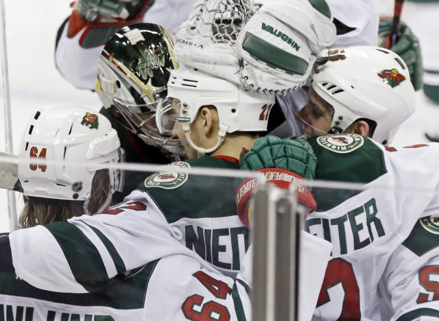 Minnesota Wild's Nino Niederreiter, center, of Switzerland, is mobbed by teammates after he scored the winning goal off Nashville Predators goalie Carter Hutton in overtime of an NHL hockey game, Thursday, Feb. 6, 2014, in St. Paul, Minn. The Wild won 3-2. (AP Photo/Jim Mone)