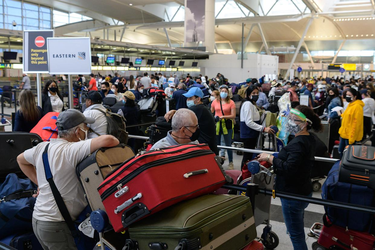 Travelers wait in line at John F. Kennedy (JFK) Airport ahead of Memorial day weekend on May 28 in New York City. (Photo by ANGELA WEISS/AFP via Getty Images)