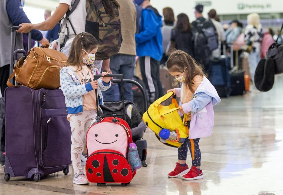 young girls masked at airport with luggage