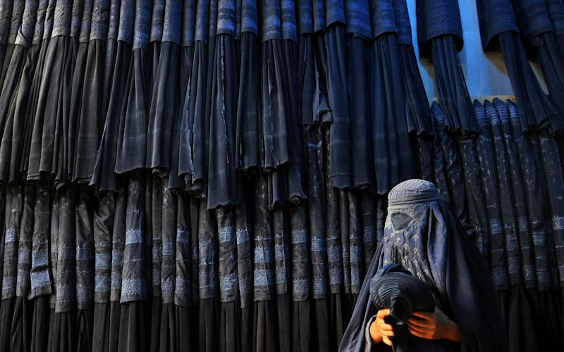 An Afghan woman buying a burka - EPA/SAYED MUSTAFA
