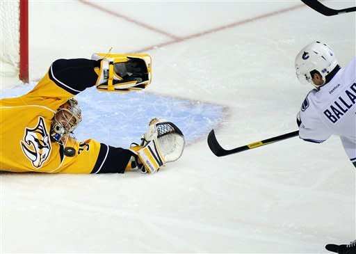 Nashville Predators goalie Pekka Rinne, left, of Finland, stops a shot on goal by Vancouver Canucks defenseman Keith Ballard, right, during the third period of an NHL hockey game on Tuesday, Feb. 7, 2012, in Nashville, Tenn. (AP Photo/Mike Strasinger)