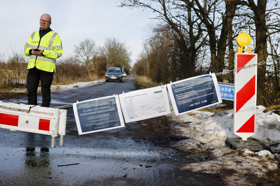 A Danish police officer guards a closed border crossing near Handewitt, Germany, Saturday, Feb. 20, 2021. Denmark has closed several smaller border crossings to Germany because of the coronavirus situation in the region near the city of Flensburg. (Frank Molter/dpa via AP)