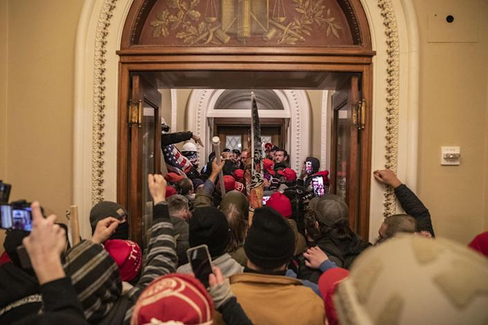 Supporters of President Donald Trump walk through the Capitol after breaching barricades to the building on Jan. 6, 2021.