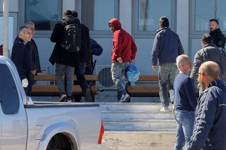Undocumented migrants are transferred to the police headquarters after being arrested during an operation to dismantle an international smuggling ring at the city of Heraklion on the island of Crete