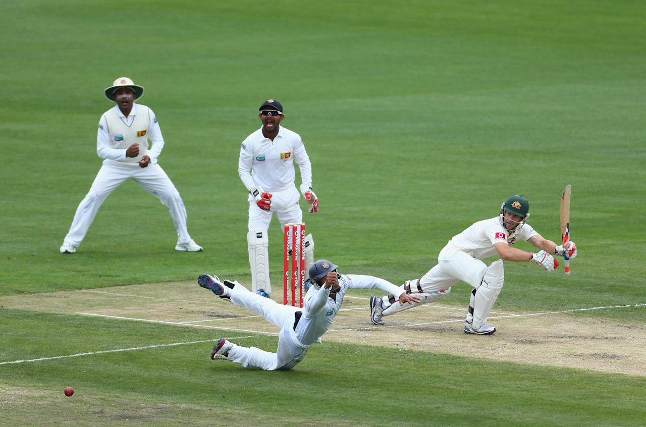 HOBART, AUSTRALIA - DECEMBER 15:  Matthew Wade of Australia gets his shot past Dimuth Karunaratne of Sri Lanka during day two of the First Test match between Australia and Sri Lanka at Blundstone Arena on December 15, 2012 in Hobart, Australia.  (Photo by Robert Cianflone/Getty Images)