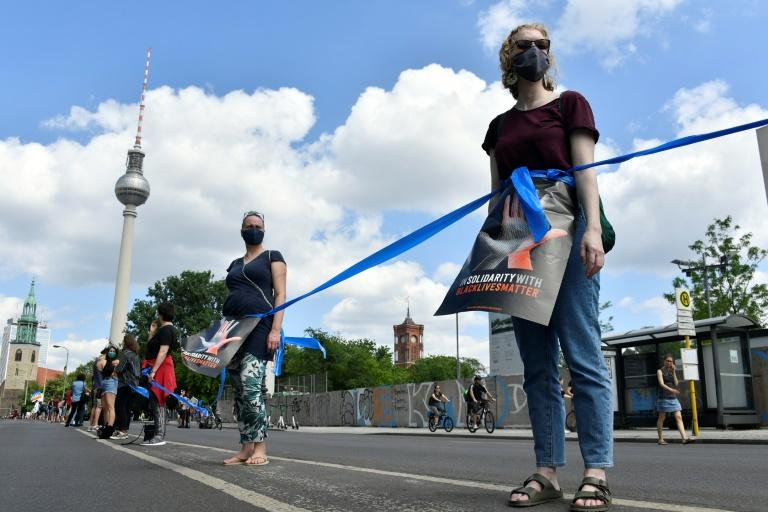 "Protesters wear face masks and form a human chain as they take part in a demonstration organised by the ""#unteilbar"" (indivisible) movement in front of the Brandenburg Gate in Berlin (AFP Photo/John MACDOUGALL)"