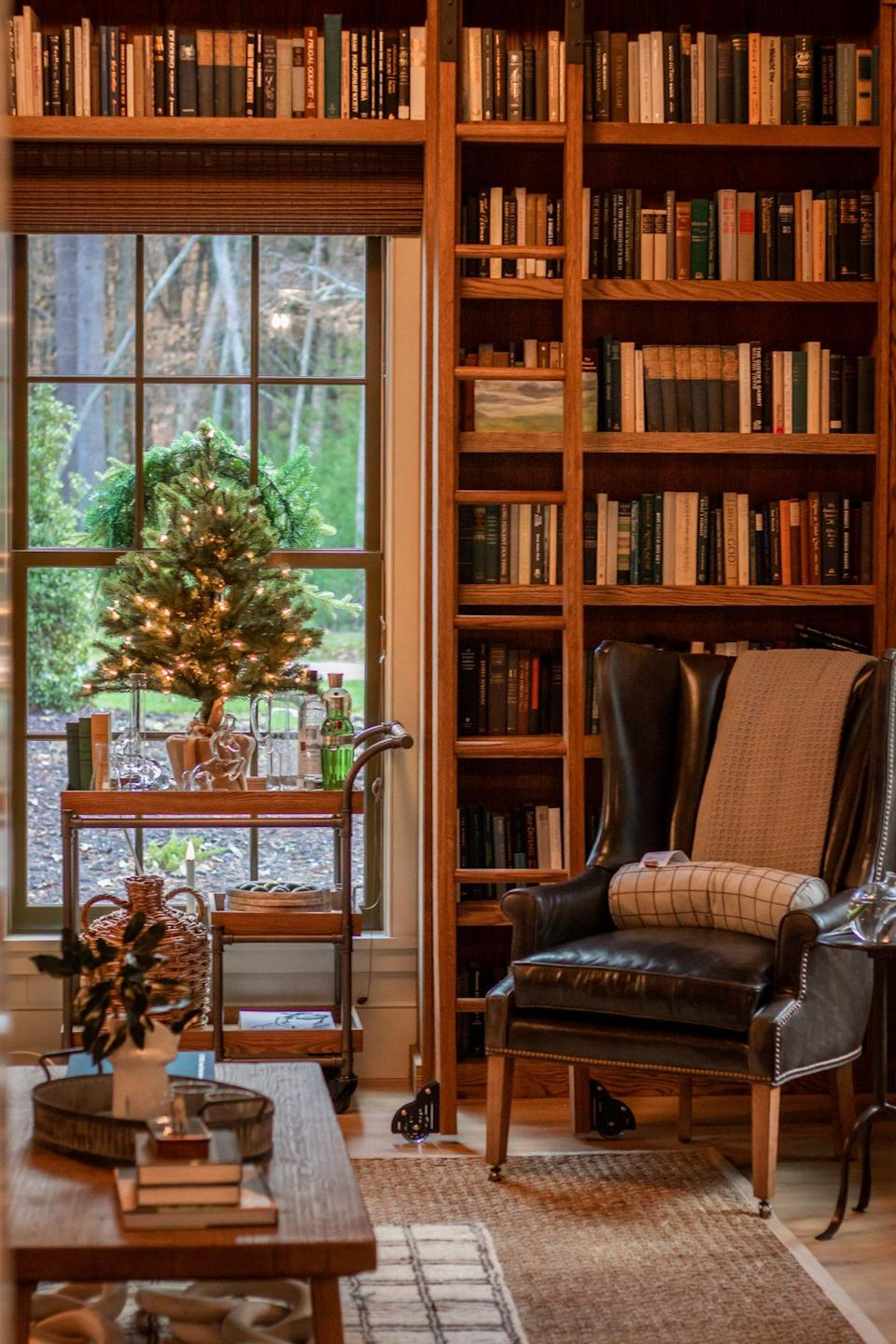 <p>The library already feels festive with its high-gloss green ceiling. A twinkling tabletop tree set on the bar cart and magnolia clippings arranged in a vase on the coffee table feel just right.</p>