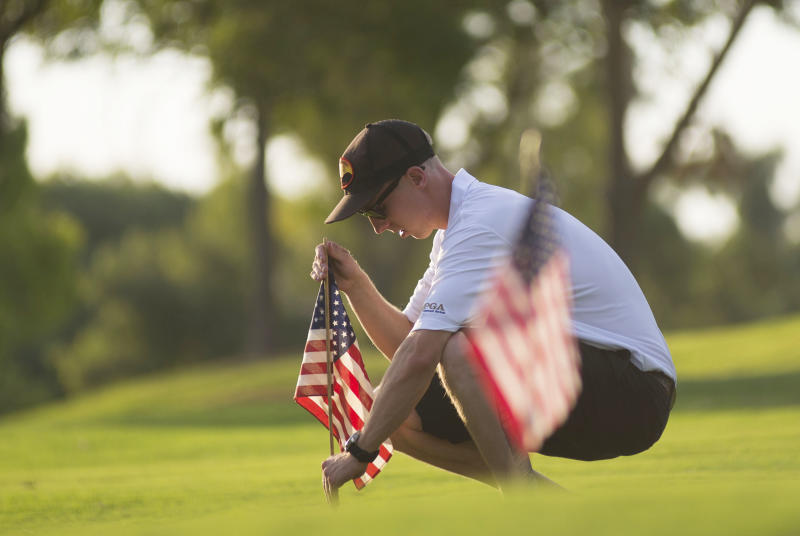 Brendan McDonough, the surviving 20th member of the Granite Mountain Hot Shots, makes sure that an American flag stands upright on a practice green at Gainey Ranch Golf Club in Scottsdale during a charity golf tournament Friday Aug. 2, 2013. (AP Photo/The Arizona Republic, Aaron Lavinsky) NO SALES, NO MAGS