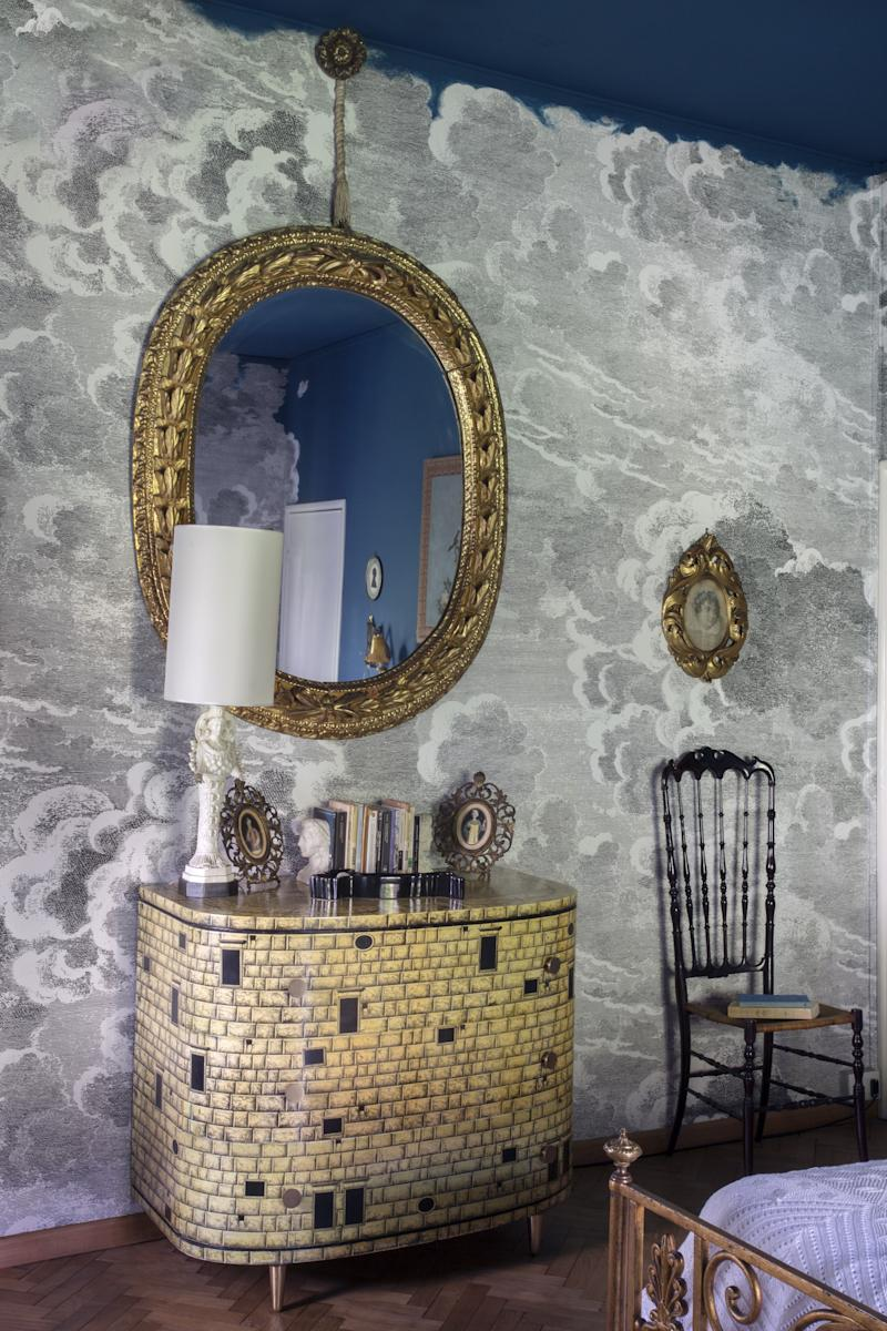"""There are several guest bedrooms in Barnaba Fornasetti's Milan home. One is soaked entirely in the color red—from the floors, walls, and table lamps to the 300-plus books with """"red"""" in their titles. It's an intense effect, and Barnaba admits that guests don't last long staying in this room. Another guest room, however, is seemingly designed for magical dreams and endless stays. The walls are lined in Fornasetti Nuvole al Tramonto wallpaper by Cole & Son, and the ceiling is painted in the blue of a moonlit sky. A soft light from garden-view windows illuminates the room which features Piero Fornasetti's 1950s Architettura drawers, Giuseppe Gaetano Descalzi's 1950s Chiavarina chair (originally designed by and produced by Fratelli Levaggi) and an 18th-century Italian oval wood mirror."""