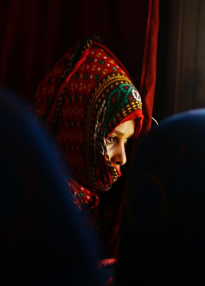An illegal migrant from Eritrea sits on a bus at the al-Laffa border crossing in Sudan's eastern Kassala state on the Eritrea-Sudan border as she is deported from Sudan back to her homeland on May 2, 2017 (AFP Photo/ASHRAF SHAZLY)