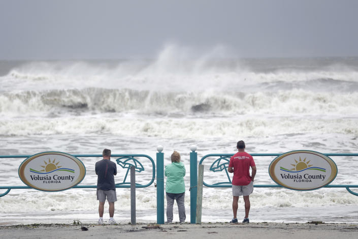 Sightseers watch waves crash on shore as Hurricane Dorian made it's way off the Florida coast Wednesday, Sept. 4, 2019, in Ormond Beach, Fla. (Photo: John Raoux/AP)
