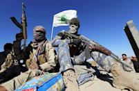 Masked Shi'ite fighters hold their weapons in Al Hadidiya, south of Tikrit, en route to the Islamic State-controlled al-Alam town, Iraq in this March 6, 2015 file photo. REUTERS/Thaier Al-Sudani/Files