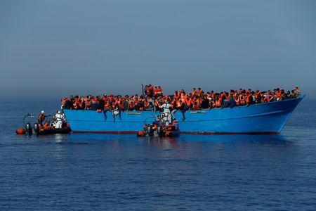 FILE PHOTO: Migrants on a wooden boat are rescued by the Malta-based NGO Migrant Offshore Aid Station (MOAS) in the central Mediterranean