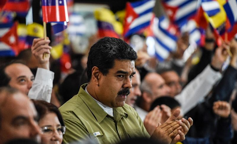Venezuelan President Nicolas Maduro applauds during a ceremony honouring Cuban leader Fidel Castro one day after Castro's death, in Caracas, on November 26, 2016 (AFP Photo/Juan Barreto)
