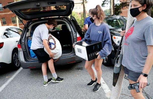 PHOTO: Miranda Darwin, from Raleigh and a freshman at UNC-Chapel Hill, center, gets help from her brother, Sam, and her mother Stacy while moving out of her room at Hinton James residence hall, Tuesday, Aug. 18, 2020, in Chapel Hill, N.C. (Ethan Hyman/The News & Observer via AP)