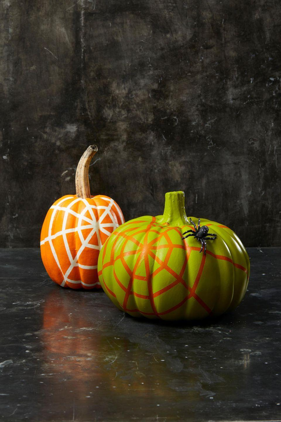 "<p>Use long strips of tape to create a web pattern on a pumpkin. Then, spray light, even strokes of spray paint over the entire surface, letting it dry completely and adding additional coats when needed. Once fully dry, carefully peel off the tape. Glue on a fake spider to complete!</p><p><a class=""link rapid-noclick-resp"" href=""https://www.amazon.com/Muzboo-Realistic-Plastic-Halloween-Decorations/dp/B07CVJ3LBN/?tag=syn-yahoo-20&ascsubtag=%5Bartid%7C10055.g.1714%5Bsrc%7Cyahoo-us"" rel=""nofollow noopener"" target=""_blank"" data-ylk=""slk:SHOP FAKE SPIDERS"">SHOP FAKE SPIDERS</a></p>"