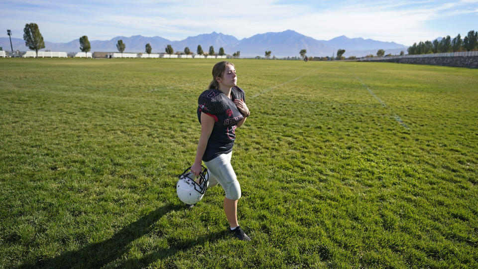 Sam Gordon walks across a field, Oct. 20, 2020, in Herriman, Utah. Gordon was the only girl in a tackle football league when she started playing the game at age 9. Now, Gordon hopes she can give girls a chance to play on female-only high school teams through a lawsuit. (AP Photo/Rick Bowmer)