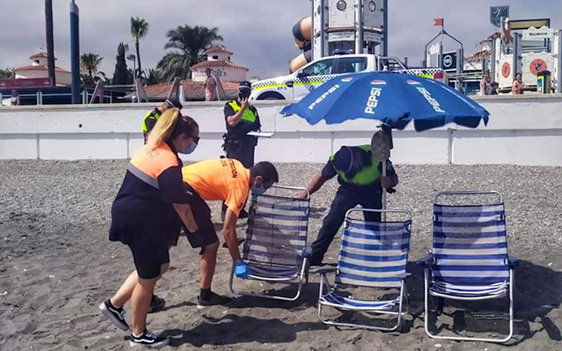 Police and beach patrol officers remove folding chairs and tables from a beach on the Costa del Sol - ASA/GC/SM
