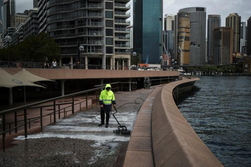 A worker cleans the waterfront area of the Sydney Opera House