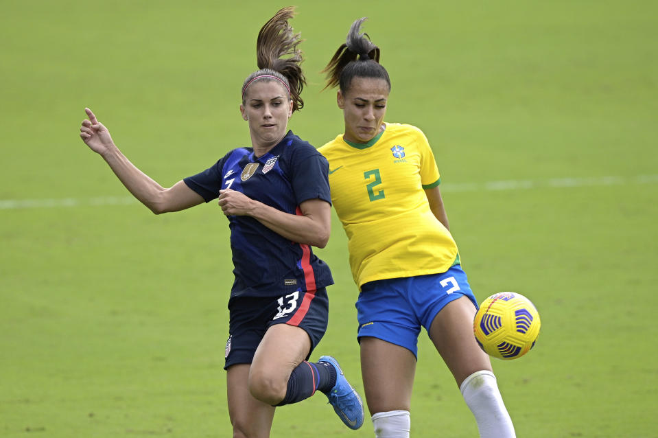 United States forward Alex Morgan (13) and Brazil defender Kathellen (2) compete for a ball during the first half of a SheBelieves Cup women's soccer match, Sunday, Feb. 21, 2021, in Orlando, Fla. (AP Photo/Phelan M. Ebenhack)