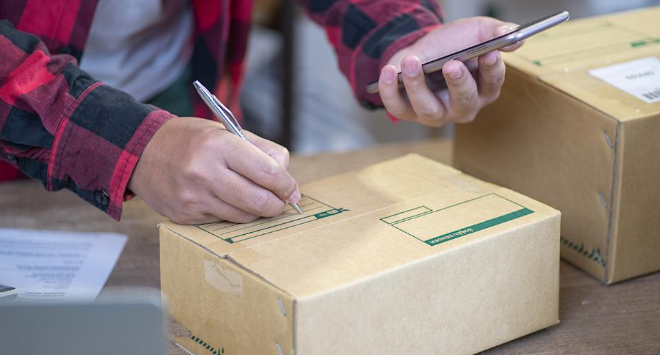 A man writes on a package. Source: Getty Images