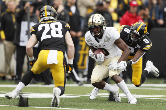 Purdue wide receiver David Bell, center, catches a pass between Iowa defenders Jack Koerner, left, and Matt Hankins, right, during the first half of an NCAA college football game, Saturday, Oct. 19, 2019, in Iowa City, Iowa. (AP Photo/Charlie Neibergall)