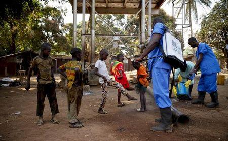 Children come forward to get their feet disinfected after a Red Cross worker explained that they are spraying bleach, and not spraying the village with the Ebola virus, in Forecariah
