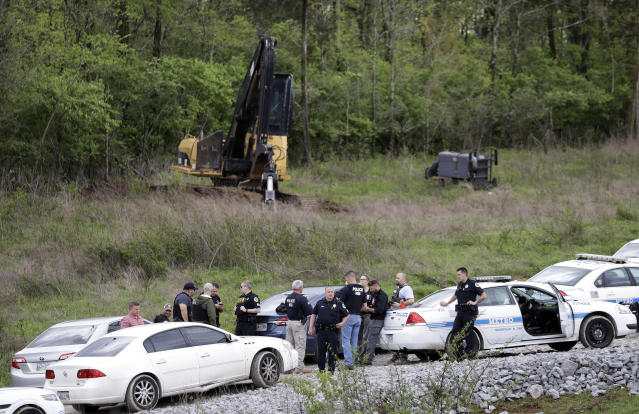 <p>Police gather on a road next to construction equipment in a wooded area near where Waffle House shooting suspect Travis Reinking was captured, Monday, April 23, 2018, in Nashville, Tenn. Police say Reinking shot and killed at least four people at the nearby restaurant in Nashville the day before. (Photo: Mark Humphrey/AP) </p>