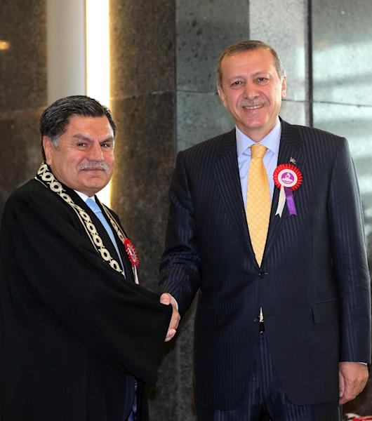 Constitutional Court Chief Justice Hasim Kilic, left, shakes hands with Prime Minister Recep Tayyip Erdogan in Ankara, Turkey, Friday, April 25, 2014. Turkey's most senior judge has delivered a sharp rebuke to Prime Minister Recep Tayyip Erdogan for criticizing his court's decisions, including one that lifted a ban on Twitter on the grounds that it violated freedoms. Erdogan reluctantly complied with the high court ruling to unblock Twitter earlier this month. Erdogan said, however, that he did not respect the ruling and described it as being against national interests. (AP Photo)
