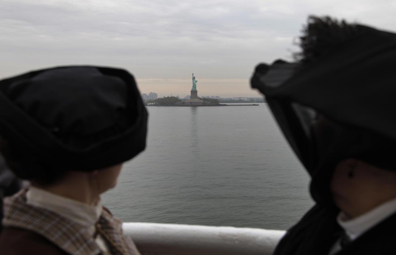 Backdropped by the Statue of Liberty, passengers Maurine Beechler, right, and her daughter my Marie Beechler,  both from Buffalo, NY, pause as the MS Balmoral Titanic memorial cruise ship, approaches at New York City port, Thursday, April 19, 2012. Exactly 100 years after the Titanic went down, the cruise retraced the ship's voyage, departing from Southampton, England, included a visit Sunday, April 15, to the location where it sank, then a stop in Halifax, Canada and final destination at New York, as of the original intended trip. (AP Photo/Lefteris Pitarakis)