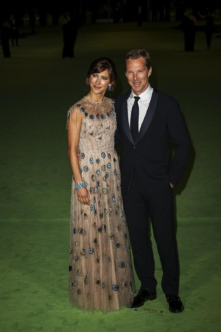 A woman in a patterned dress and a man in a black suit and tie posing on a green carpet