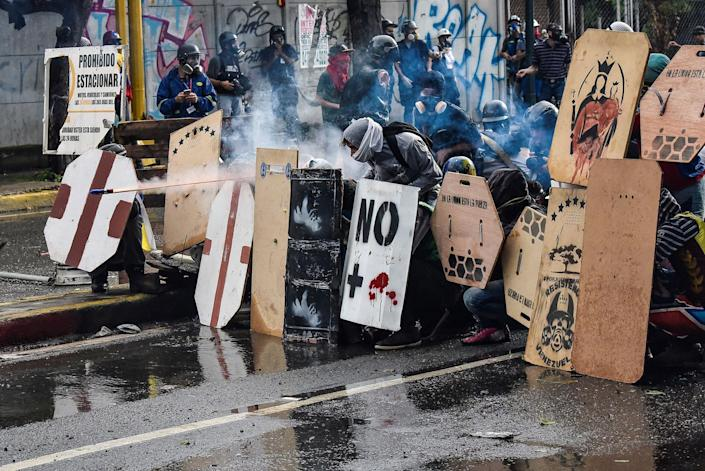<p>Protesters take cover behind home made shields and throw fireworks at the national guard members during clashes in Caracas, Venezuela on July 28, 2017. (Photo: Carlos Becerra/Anadolu Agency/Getty Images) </p>