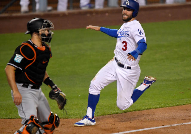 Los Angeles Dodgers' Chris Taylor, right, scores on a sacrifice fly hit by Cody Bellinger as Miami Marlins catcher J.T. Realmuto waits for the ball during the eighth inning of a baseball game, Monday, April 23, 2018, in Los Angeles. (AP Photo/Mark J. Terrill)