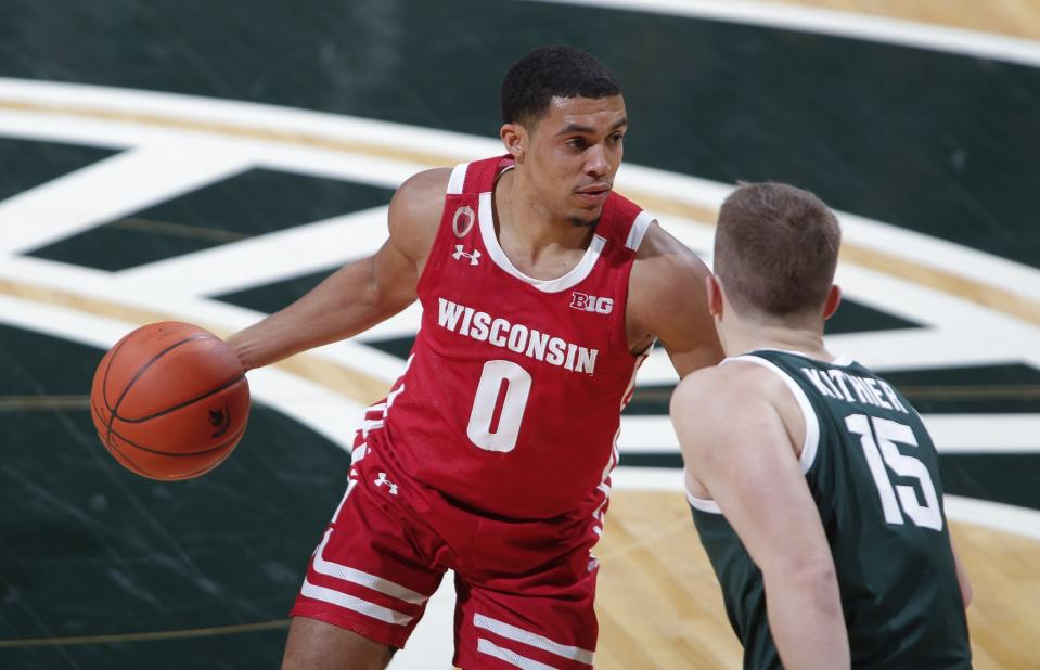 Wisconsin's D'Mitrik Trice, left, drives against Michigan State's Thomas Kithier during the first half of an NCAA college basketball game, Friday, Dec. 25, 2020, in East Lansing, Mich. Wisconsin won 85-76. (AP Photo/Al Goldis)