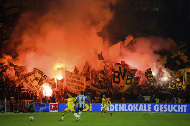 Dortmund fans in the guest block of the stadium wave flags and igniting pyrotechnics during a German Bundesliga soccer match between Hertha BSC Berlin and Borussia Dortmund in Berlin. Germany, Saturday, Novc.30, 2019. (Gregor Fischer/dpa via AP)