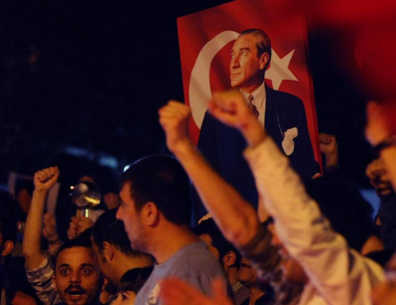 """Thousands of Turkish protesters, holding national flags and portraits of Turkey's founder Mustafa Kemal Ataturk, jubilate as they march in Turkish capital, Ankara, Thursday, June 6, 2013.  Turkish Prime Minister Recep Tayyip Erdogan on Thursday appeared to have slightly moderated his rhetoric regarding the anti-government protests in his country but didn't back away from redevelopment plans for Istanbul that sparked the nearly week-long unrest and claimed """"terrorist groups"""" were involved in the unrest.    (AP Photo/Burhan Ozbilici)"""