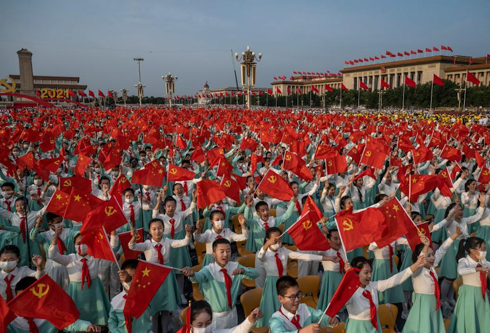 Chinese students wave party and national flags at the 100th anniversary ceremony.