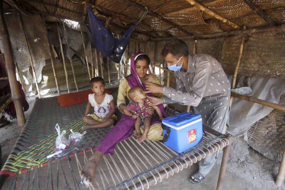 A health worker gives a polio vaccine to a child at a slum area in Lahore, Pakistan, Saturday, Aug. 15, 2020. Pakistani government launched an anti-polio vaccination campaign in an effort to eradicate the crippling disease affected children. (AP Photo/K.M. Chaudary)