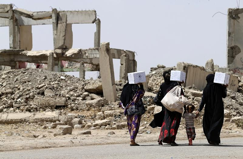Iraqi women walk past destroyed buildings south of Mosul on May 26, 2017 (AFP Photo/KARIM SAHIB)