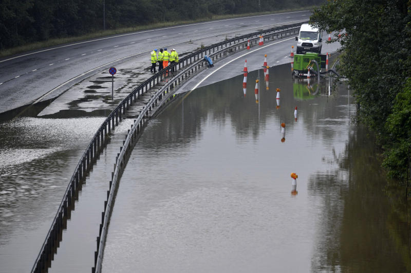 Workers inspect the flooded main roadway in Stockport, England, after parts of the region were inundated by overnight rain, Wednesday July 31, 2019. Many parts of the region have had heavy rain over the past 24 hours, with forecasts predicting the possibility of more rain to come. (Danny Lawson/PA via AP)