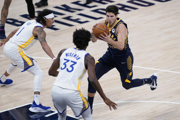 Indiana Pacers' Doug McDermott (20) goes to the basket against Golden State Warriors' Damion Lee (1) and James Wiseman (33) during the first half of an NBA basketball game Wednesday, Feb. 24, 2021, in Indianapolis. (AP Photo/Darron Cummings)