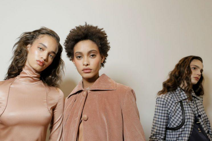 Three models pose against a white backdrop.