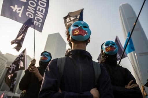 Some protesters at a rally for China's Uighurs in Hong Kong wore blue face masks with the flag of East Turkestan, the term many Uighur separatists use for Xinjiang