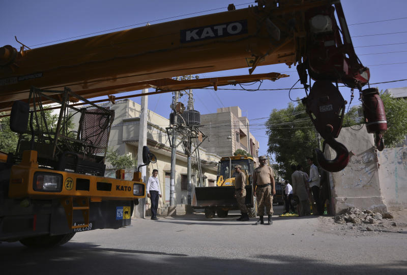 Pakistan army soldiers stand beside the heavy machinery park on a street leading to the site of a plane crash, in Karachi, Pakistan, Sunday, May 24, 2020. A passenger plane belonging to state-run Pakistan International Airlines carrying passengers and crew crashed Friday near the southern port city of Karachi. (AP Photo/Fareed Khan)
