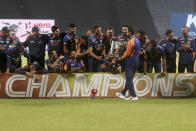 Members of the Indian team celebrate as captain Virat Kohli walks with the winners trophy after their win in the third One Day International cricket match between India and England at Maharashtra Cricket Association Stadium in Pune, India, Sunday, March 28, 2021. India won the series 2-1. (AP Photo/Rafiq Maqbool)