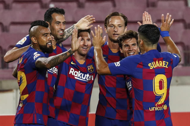 FC Barcelona players celebrate their opening goal during the Spanish La Liga soccer match between FC Barcelona and Atletico Madrid at the Camp Nou stadium in Barcelona, Spain, Tuesday, June 30, 2020. (AP Photo/Joan Monfort)