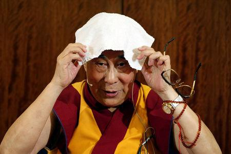 FILE PHOTO: Tibet's exiled spiritual leader the Dalai Lama puts a towel on his head during a news conference in Paris
