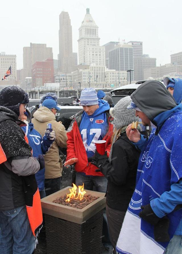 Fans keeps warm while tailgating outside Paul Brown Stadium prior to an NFL football game between the Cincinnati Bengals and the Indianapolis Colts, Sunday, Dec. 8, 2013, in Cincinnati. (AP Photo/Tom Uhlman)