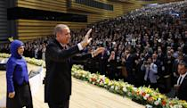 Turkish Prime Minister Recep Tayyip Erdogan (R) waves to members of the ruling Justice and Development Party (AKP), flanked by his wife Emin Erdogan, at a ceremony in Ankara on July 1, 2014 (AFP Photo/Umit Bektas )