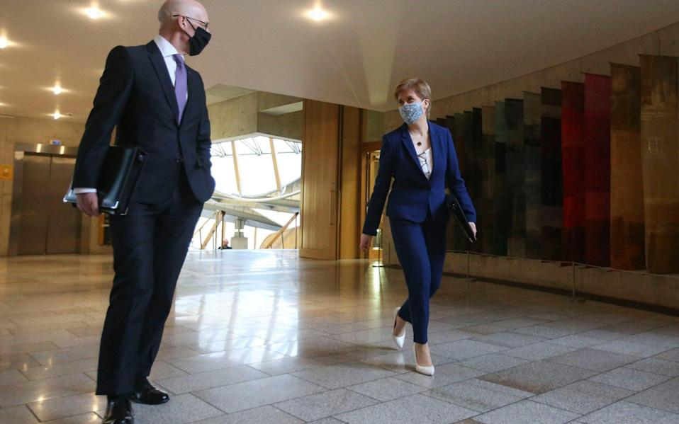 First Minister Nicola Sturgeon and Deputy First Minister John Swinney arrive for First Minister's Questions (FMQs) in the debating chamber of the Scottish Parliament in Edinburgh - PA